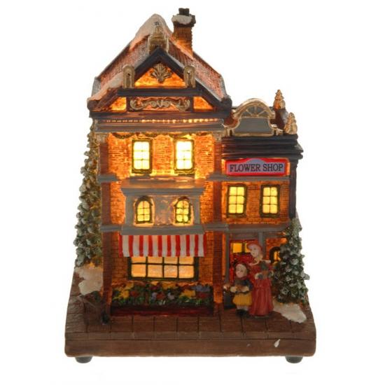 Kersthuisje bloemenwinkel met verlichting